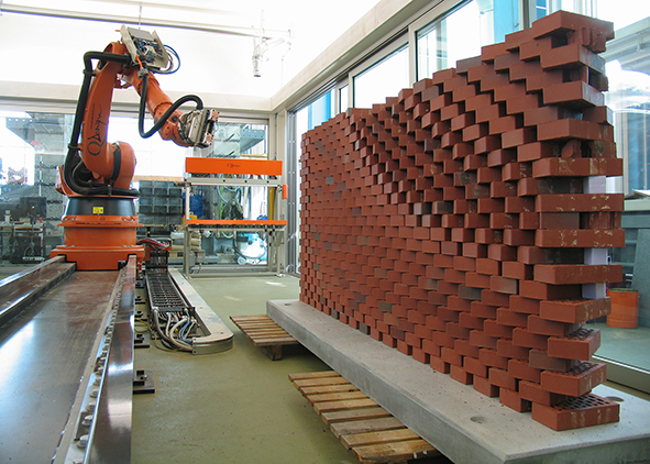 Robot (Pin) laying hollow bricks on a construction site (photo by Tibbo)